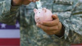 Dinheiro de colocação militar masculino no mealheiro, bom financiamento do exército, salário aceitável vídeos de arquivo