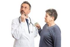 Dinheiro de colocação paciente dentro do bolso do doutor fotografia de stock