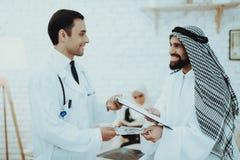 Dinheiro de doação paciente árabe dos dólares a medicar imagens de stock royalty free