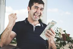Dinheiro de m?o feliz do homem foto de stock royalty free
