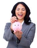 Dinheiro de riso da economia da mulher de negócios em um piggybank Imagens de Stock