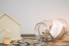 Dinheiro de salvamento com a mão que põe moedas no vidro do frasco, nas economias e no dinheiro do investimento para para prepara fotografia de stock