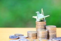 Dinheiro de salvamento, fazendo a um pássaro do origâmi a cédula tailandesa na pilha de dinheiro das moedas no fundo verde natura foto de stock
