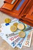 Dinheiro do Euro - cédulas e moedas - na carteira marrom Foto de Stock