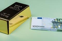 Dinheiro do Euro e barra de ouro em um fundo verde banknotes Dinheiro conta ingot bullion imagens de stock