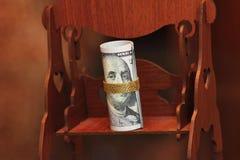 Dinheiro do rolo das notas de dólar com a corrente do ouro no balanço de madeira do brinquedo Imagens de Stock