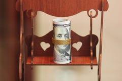Dinheiro do rolo das notas de dólar com a corrente do ouro no balanço de madeira do brinquedo Imagem de Stock Royalty Free