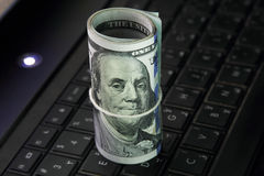 Dinheiro do rolo das notas de dólar no teclado do portátil Imagem de Stock