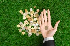 Dinheiro e assunto da finança: Moedas do dinheiro e mão humana no terno preto que mostra o gesto em um fundo da opinião superior  fotografia de stock