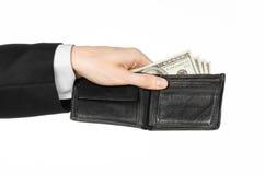 Dinheiro e assunto do negócio: mão em um terno preto que guarda uma carteira com as cédulas do dólar isoladas no fundo branco no  Foto de Stock Royalty Free
