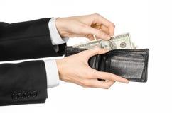 Dinheiro e assunto do negócio: mão em um terno preto que guarda uma carteira com as cédulas do dólar isoladas no fundo branco no  Fotografia de Stock Royalty Free