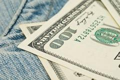 Dinheiro e bolso das calças de brim. 100 dólares Foto de Stock