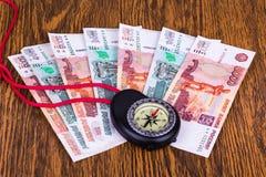 Dinheiro e compasso na tabela Fotos de Stock Royalty Free