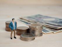 Dinheiro e conceito do negócio Figura pequena posição do homem de negócios Fotos de Stock