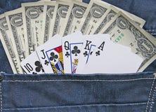 Dinheiro e jogo no bolso das calças de brim da sarja de Nimes Foto de Stock