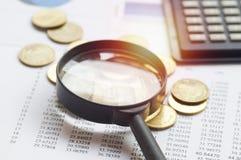 dinheiro e lente de aumento da moeda da pilha Imagens de Stock Royalty Free