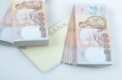 Dinheiro e livro de conta tailandeses Imagens de Stock