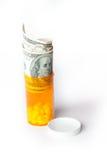 Dinheiro e medicamentos de venta com receita em um recipiente com cem notas de dólar Foto de Stock