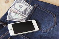 Dinheiro e smartphone (dispositivo) no woodbackground Fotos de Stock