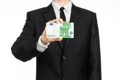 Dinheiro e tema do negócio: um homem em um terno preto que guarda uma conta de 100 euro e mostras um gesto de mão em um backgrou  Fotos de Stock Royalty Free