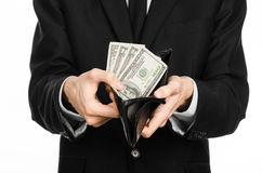Dinheiro e tema do negócio: um homem em um terno preto que guarda uma bolsa com os dólares do papel moeda isolados no fundo branc Fotografia de Stock