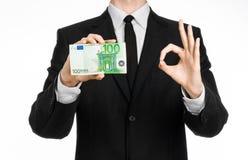Dinheiro e tema do negócio: um homem em um terno preto que guarda uma conta de 100 euro e mostras um gesto de mão em um backgrou  Fotografia de Stock Royalty Free