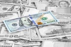 Dinheiro em multi moedas com conta de 100 USD na parte superior Imagem de Stock