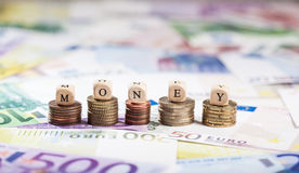Dinheiro em pilhas da moeda, fundo da palavra do dinheiro Foto de Stock
