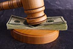 Dinheiro entre o martelo do ` s do juiz e o close-up do suporte em um fundo de pedra fotografia de stock royalty free