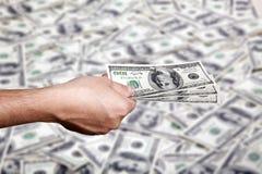 Dinheiro entregando sobre o fundo do dinheiro Fotografia de Stock Royalty Free