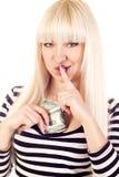 Dinheiro escondendo bonito da mulher nova que diz o shh Imagens de Stock Royalty Free