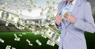 Dinheiro escondendo da mulher de negócios no revestimento no estádio de futebol que representa a corrupção imagem de stock