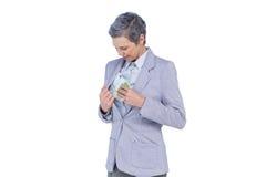 Dinheiro escondendo da mulher de negócios em seu terno Fotos de Stock