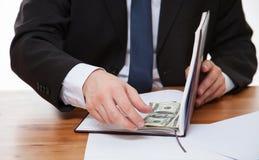 Dinheiro escondendo do homem de negócios no livro Fotos de Stock Royalty Free