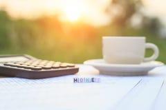 Dinheiro escrito em grânulos da letra e um copo de café na tabela Fotos de Stock Royalty Free