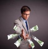 Dinheiro estando e de jogo do homem novo Fotografia de Stock