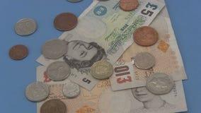 Dinheiro esterlino e moedas BRITÂNICOS que giram um fundo azul vídeos de arquivo