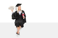Dinheiro guardando graduado da fêmea assentado em um painel Foto de Stock