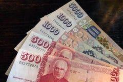 Dinheiro islandês Dinheiro de Islândia Diversas contas da coroa islandêsa na tabela de madeira A coroa islandêsa é a moeda nacion fotografia de stock