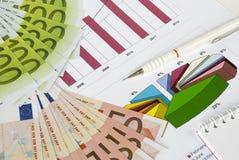 Dinheiro, lápis e caderno em um gráfico Fotos de Stock Royalty Free