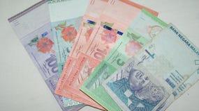 Dinheiro malaio no fone branco Foto de Stock