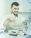 Dinheiro masculino do salário do gerente eficazmente em linha fotografia de stock