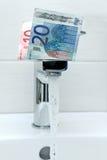 Dinheiro na torneira e na água de fluxo Fotografia de Stock Royalty Free