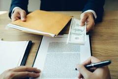 Dinheiro nas mãos dos homens de negócios que se estão submetendo aos empresários para forçar a assinatura de documentos do contra fotografia de stock royalty free