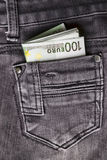 Dinheiro no bolso das calças de brim Imagem de Stock