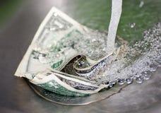 Dinheiro para baixo no dreno Imagens de Stock Royalty Free