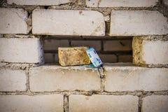Dinheiro para o trabalho sob um tijolo imagem de stock royalty free