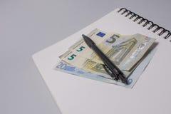 Dinheiro, pena e caderno na tabela do escritório no fundo branco Conceito do orçamento Imagem de Stock