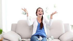 Dinheiro que cai na morena bonita no sofá vídeos de arquivo