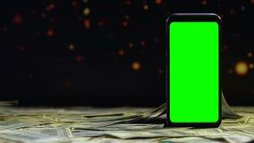 Dinheiro que cai na tabela em torno do smartphone verde da tela, salário no Internet filme